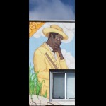 Benny More, famed as one of the greatest Cuban singers of all time, keeps watch over the mural and leads the viewer in. He played in Havana bars and cafes in the 1940's until he replaced one of the singers in Trio Matamoros, a musical trio that is also depicted in the mural. Benny later went on to gain popularity in the 1950's as he toured with his band, Banda Gigante.